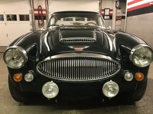 vintage Austin Healey sports car is parked inside difiore's detailing garage