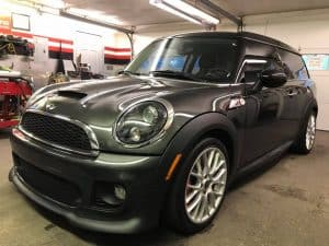 dark green mini cooper inside the detailing garage